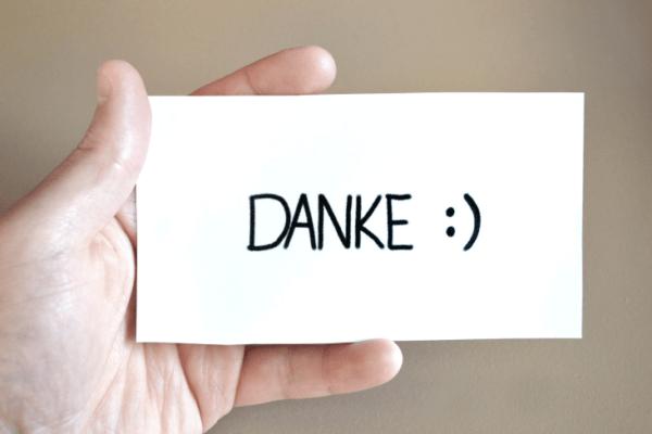 """Bild mit einer Hand, die eine Karte hält, auf der """"Danke"""" steht"""